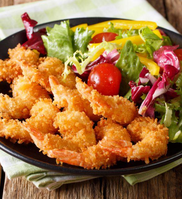 Fried shrimps tempura and fresh salad close-up on a plate. horizontal