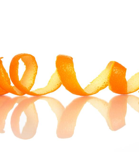 Spiral orange peel reflecting on white background.