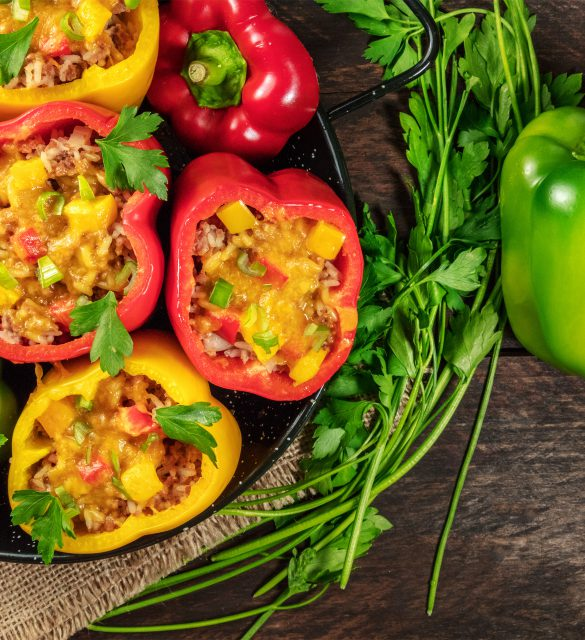 An overhead photo of stuffed bell peppers with fresh parsley and a green pepper, with a place for text