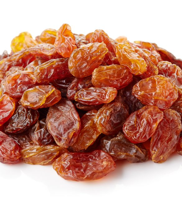 Heap of brown raisins isolated on white background