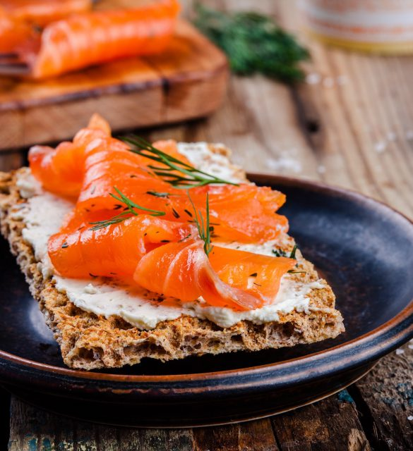 Toast with smoked salmon on wooden table