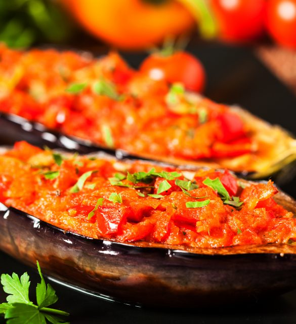 Stuffed aubergine on black plate. Wooden background. Front view.