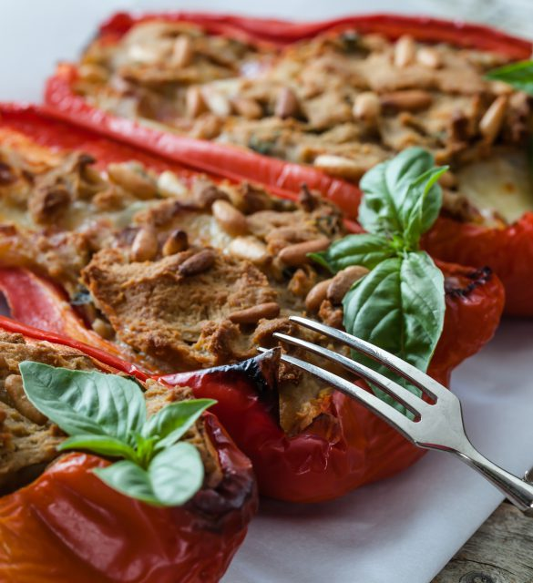 Closeup shot of baked peppers stuffed with tuna fish, mozzarella cheese and pine seeds.