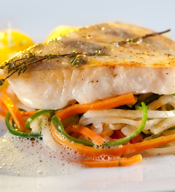 Fried pike perch with vegetables: potatoes, on stripes of carrots, cucumber and asparagus in a fluffy sauce.