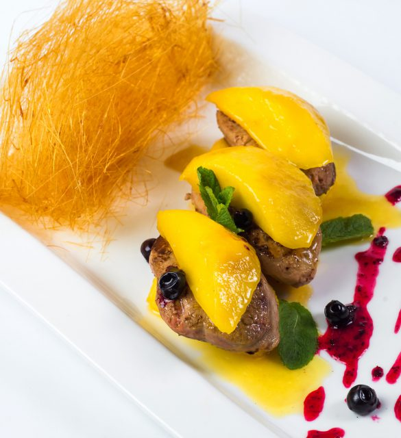 Pan seared foie gras on ripe mango and pomegranate reduction on white plate.