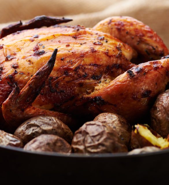 Close view at whole roasted chicken with potatoes on a wooden rustic background