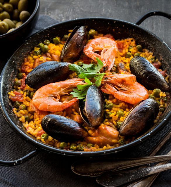 Paella in black pan with rice, shrimps, mussels, squid and meat, bowl with olives and vintage cutlery. Seafood paella, traditional spanish dish. Paella on rustic black wooden table. Selective focus