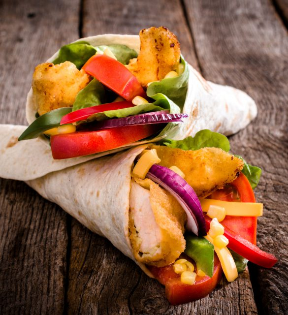 Tortilla wrap sandwich with fried chicken and vegetables on wooden background,selective focus