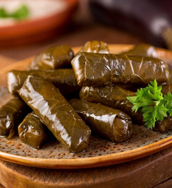 A plate of delicious stuffed grape leaves with parsley garnish.