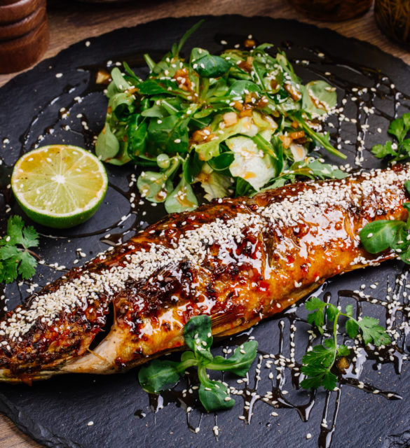 baked whole seabass grilled on a plate with vegetables and lemon  for the menu