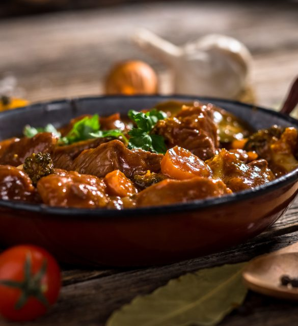 Meat stewed with vegetable on rustic wooden background