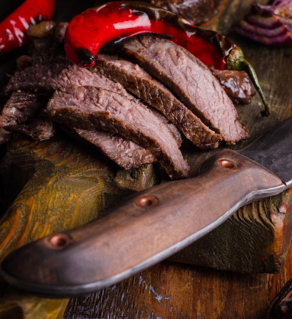 Medium rare grilled Beef steak Ribeye with knife and fork for meat on cutting board on dark wooden background